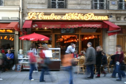Pedestrians walk by an outdoor cafe in Paris, France. I shot this in 2004.