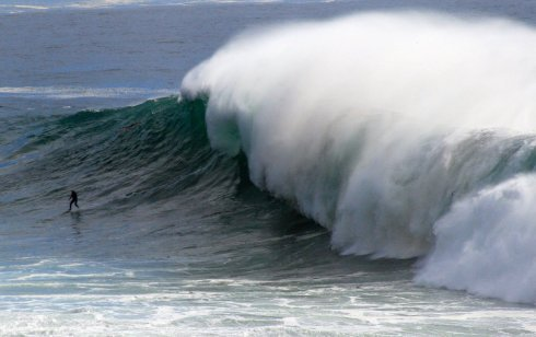 Surfer dwarfed by large wave near Pebble Beach, CA